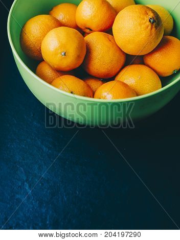 Mandarins in green plate on the black background