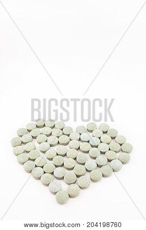 Heart made up of spirulina pills. White background. Vertical.