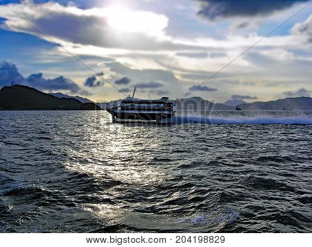 A high-speed ferry rides in the evening across the sea from Hong Kong Island to Macau