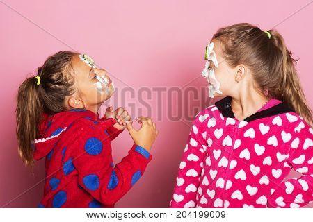 Kids Pose On Pink Background. Girls In Polka Dotted Pajamas