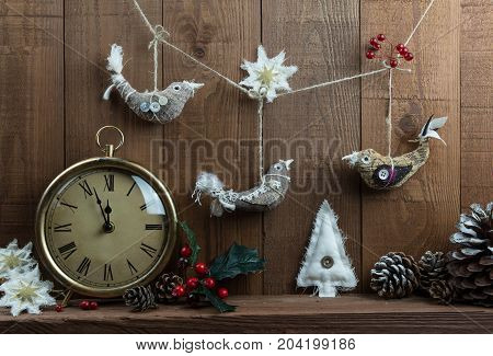 Christmas arrangement with vintage clock and homemade Christmas decorations on wooden background. With Holly berries and pine cones.