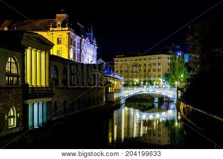 Triple Bridge city centre of Ljubljana and the River Ljubljanica illuminated at night Slovenia