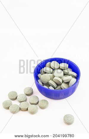 Container ble with spirulina pills. vitamin B12. White background.