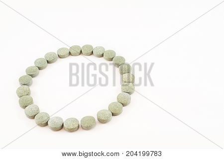 Circular contour formed by spirulina pills. Supplement of vitamin B12. White background.