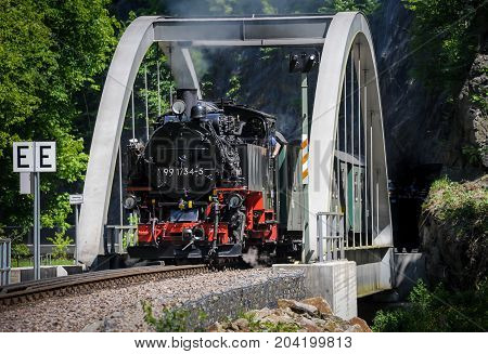 Train with a steam engine going over a bridge on a sunny day