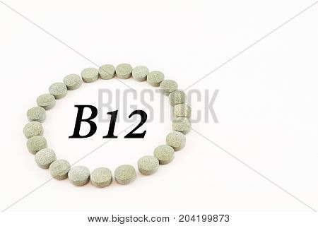 Circular outline formed by spirulina tablets with word B12 inside. Supplement of vitamin B12. White background.