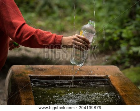 Closeup of child filling a water bottle at a fountain