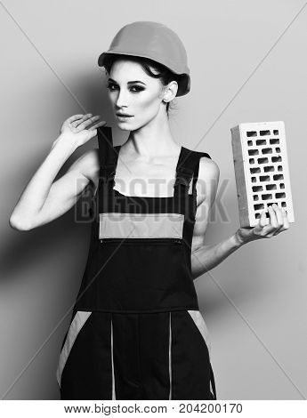 pretty cute sexy builder girl or brunette woman with fashion makeup on serious face in orange uniform with tied up hair in bun and hard hat or helmet holding brick on blue studio background