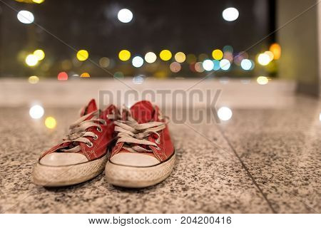 Old red jeans denim gumshoes with unleashed shoelaces on blurred background. Vintage sneakers. Traveler outfit.