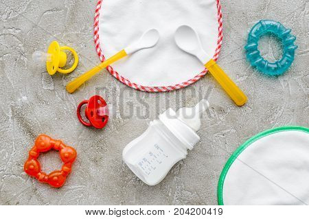bottle with breastmilk and infant formula powdered healthy food, toys and bib on stone desk background top view