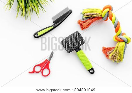 care about pet with brushes, toys and grooming equipment on white table background top view