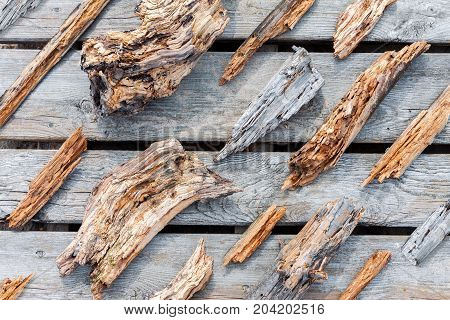 Old rotten wooden pieces and fragments well organized on wooden plank background top view