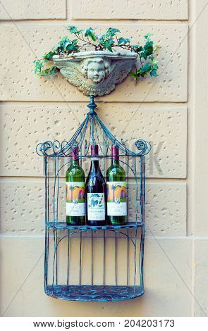 FLORENCE ITALY - JULY 12 2016: Wine shop exterior detail with decorative holder and three empty wine bottles in Florence Italy