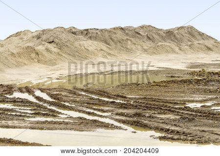 wet scenery with skidmarks around a light brown heap of earth