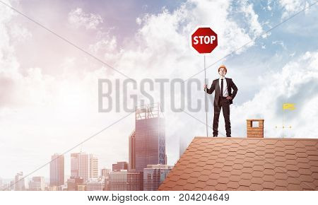 Businessman standing on house roof and holding stop sign. Mixed media