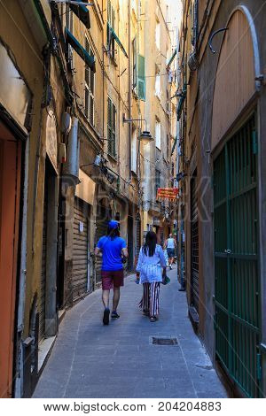 08.07.2017. Historical center of the city Genoa ( Genova ) Italy Europe. Tourist attraction. Tourists are walking along a narrow ancient street. The concept of travel and active recreation.