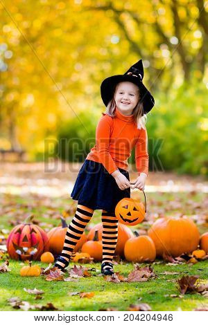 Little Girl In Witch Costume On Halloween Trick Or Treat
