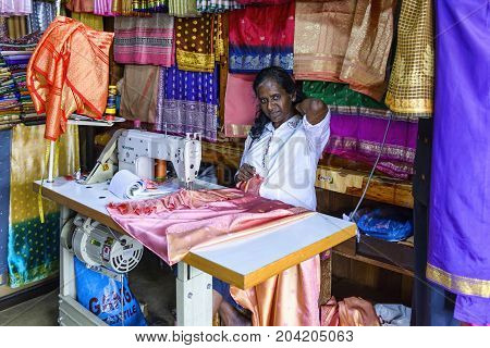Kandy, Sri Lanka - August 18, 2017: A seamstress at work in her store in Kandy central market
