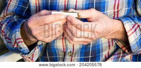 Man rolling tobacco handmade cigarette close up of hands and cigars paper - Concept of expensive legal drug addiction unhealthy lifestyle and bad habit for human health