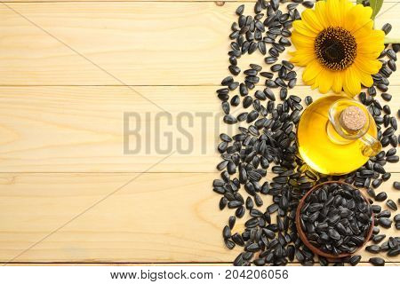 Sunflower Oil, Seeds And Flower On White Wooden Background. Top View With Copy Space