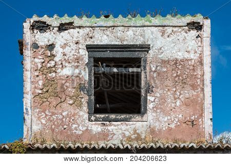 Part of an abandoned house at Sao Miguel Island Azores Islands Portugal shape of a postage stamp. Opened empty window. Blue sky.