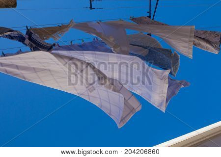 Various clean laundry hanging in the street to get dry. View from down. Bright blue sky.