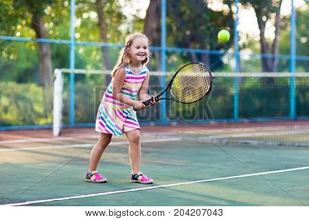 Child Playing Tennis On Outdoor Court