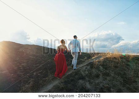 Young Couple Climbs Top Of A Mountain And Enjoying Sunset