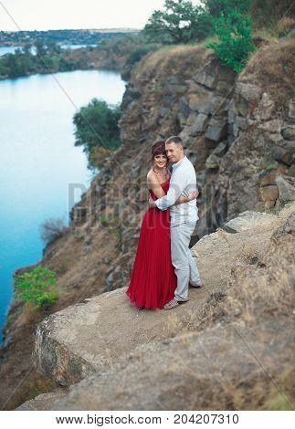 Stylish Couple Newlyweds Standing At Canyon Near A Lake. Close-up Portrait