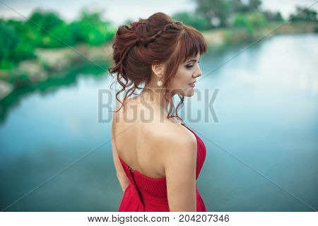 Young redhead girl in red dress on nature background. rear view Freedom concept. Fantasy. Wind