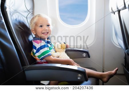 Child in airplane. Kid in air plane sitting in window seat. Flight entertainment for kids. Traveling with young children. Kids fly and travel. Family summer vacation. Baby boy with toy in airplane.