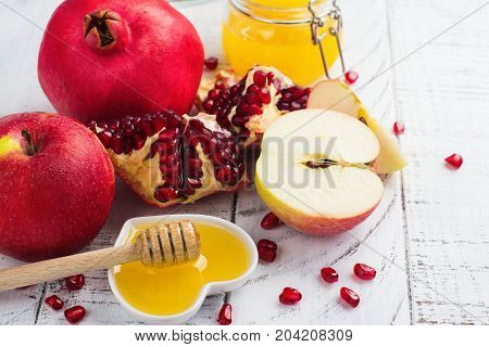 Apple, honey and pomegranate on white wooden background. Jewish New Year - Rosh Hashana concept. Space for text