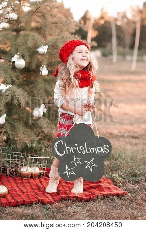 Laughing kid girl 4-5 year old having fun with christmas decorations outdoors. Winter season. Holidays.
