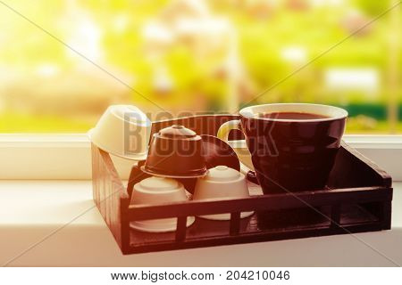 Window With Cup Of Black Coffee And Capsules Over Wooden Tray For Coffee Machine, Toned Photo