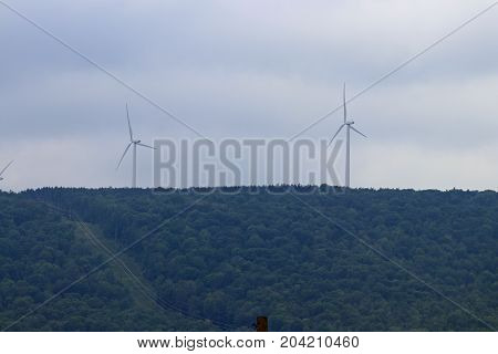 Wind turbines show their massive size next to powerlines climbing over the mountains.