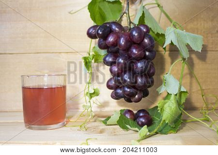 grapes on a brown background. a bunch of grapes. grapes, green leaves. dark blue grapes. juice in a glass