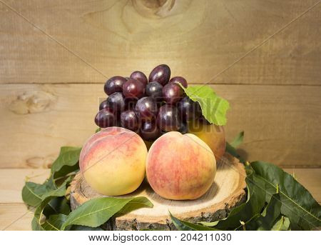 peaches and grape brown background. grapes with green leaves. a bunch of grapes. in green leaves. peaches with dark blue grapes.