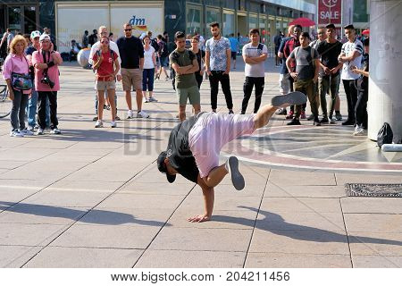 BERLIN, GERMANY - AUGUST 08, 2017: Breakdancer entertain tourists from all over the world with a performance at Alexanderplatz in the center of the city.