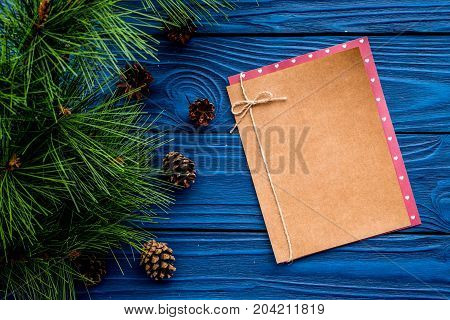 pine cones to decorate christmas tree for new year celebration with fur tree branches and notebook on blue wooden table background top veiw mockup