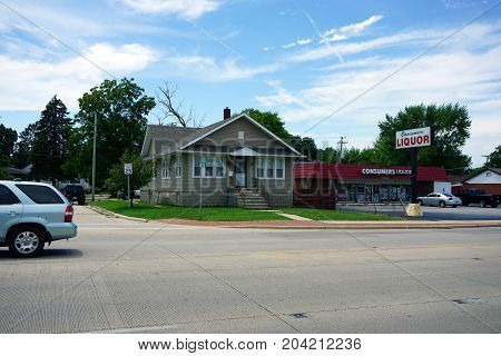 JOLIET, ILLINOIS / UNITED STATES - JULY 21, 2017: A single family home stands at the corner of Loretta Street and Plainfield Road, next to the Consumer Liquors store.