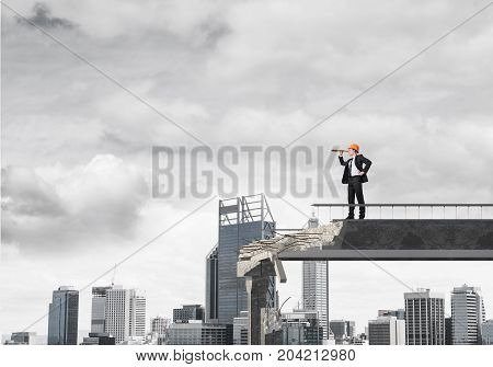 Young engineer in suit and helmet looking in spyglass while standing on broken bridge with cityscape on background. 3D rendering.