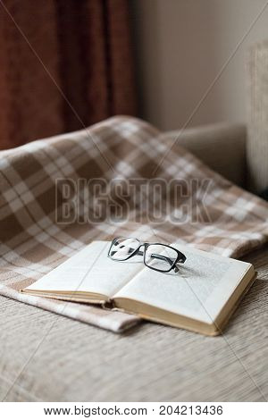A cozy sofa, a  pillow and a plaid, open book and glasses. Leisure time, reading and resting.
