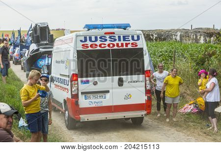 QuievyFrance - July 07 2015: The official ambulance driving on a cobblestoned road before the stage 4 of Le Tour de France 2015 in Quievy France on 07 July2015.
