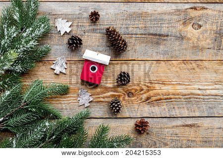 toys and pine cones to decorate christmas tree for new year celebration with fur tree branches on wooden table background top veiw mockup