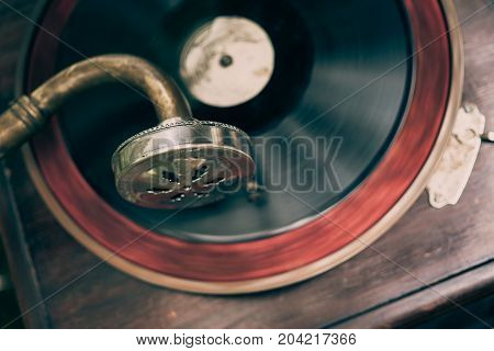 Vintage gramophone with a vinyl, top view, selective focus, toned