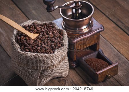 Grinding coffee from roasted beans into a rustic bag.