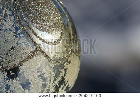 Close Look at a Frozen Golden Outdoor Christmas Ornament