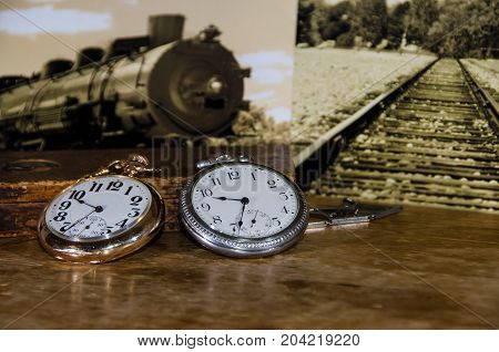 Pair of Vintage Railroad Watches Resting on a Wooden Table