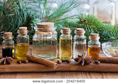 Selection of essential oils with spruce and pine branches on a wooden background with Christmas spices and ingredients in the foreground: cinnamon clove star anise frankincense