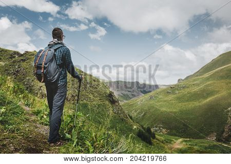 Hiker Man With Backpack And Trekking Poles Resting And Looking At The Mountains In Summer Outdoor Rear View